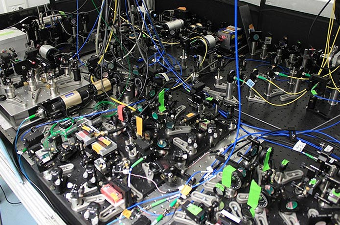 <p>Some of the lasers and optics used in the ACME experiment. (Photo credit: Loic Anderegg)</p>