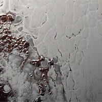 <p>Close-up of Sputnik Planum shows the slowly overturning cells of nitrogen ice. Boulders of water ice and methane debris (red) that have broken off hills surrounding the heart have collected at the boundaries of the cells. (Photo: NASA/Johns Hopkins University Applied Physics Laboratory/Southwest Research Institute)</p>