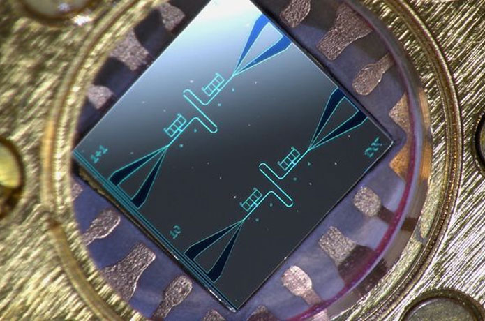 <p>Photo of a centimeter-sized silicon chip, which has two parallel superconducting resonators and quantum-circuit refri
