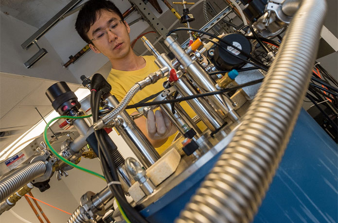 <p>Former Rice University graduate student Xinwei Li in 2016 with the terahertz spectrometer he later used to measure en